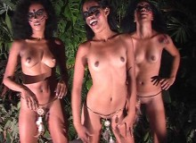 Three wild exotic chicks with painted faces and feathers on belts dancing ethnic dances in the nigh tropical forest